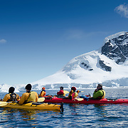 Kayakers admire the impressive scenery on a clear sunny day at Cuverville Island on the Antarctic Peninsula.