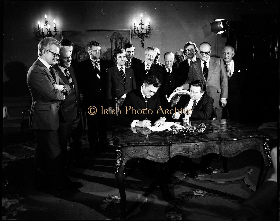 29/03/1976<br /> 03/29/1976<br /> 29 March 1976<br /> Petroleum exploration licences signed at Iveagh House, Dublin. Minister for Industry and Commerce, Mr Justin Keating T.D. and senior oil company executives representing the firms to which licences were being granted signed petroleum exploration licences in respect of exploration offshore of Ireland. Image shows The Minister (seated right) signing the licence with Mr P.W.J. Wood, President Ireland-Cities Services Inc., on behalf of Cities Services group including Skelly Petroleum Ireland Ltd., British Gas Coporation and Gaelic Oil Ltd.