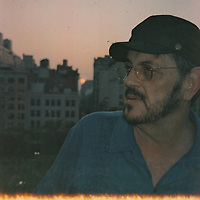 """1. When was this photo taken?<br /> <br /> 2004<br /> <br /> 2. Where was this photo taken?<br /> <br /> Union Square Park<br /> <br /> 3. Who took this photo?<br /> <br /> I did<br /> <br /> 4. What are we looking at here?<br /> <br /> We are looking at my husband, Robert, deep in thought as the sun sets between Manhattan buildings.<br /> <br /> 5. How does this old photo make you feel?<br /> <br /> Currently, I feel awe, for my husband died this year. This """"Lost Photo"""" is a gift. The photo captured his strong presence in life and in my life.<br /> <br /> 6. Is this what you expected to see?<br /> <br /> No. the photo was a wonderful surprise<br /> <br /> 7. What kind of memories does this photo bring back?<br /> <br /> Memories of walks and talks we had. He was my best friend. He seems to be emerging into the photo as he emerged into my life and enriched it.<br /> <br /> 8. How do you think others will respond to this photo?<br /> <br /> I think they will see the strength in the man, his strong presence and engagement with life; that he was a man with a deep soul."""