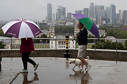 © Licensed to London News Pictures. 08/08/2021. London, UK. Members of the public use umbrellas to shelter from rain in Greenwich Park in South East London. A yellow weather warning for thunderstorms is in place for parts of England. Photo credit: George Cracknell Wright/LNP
