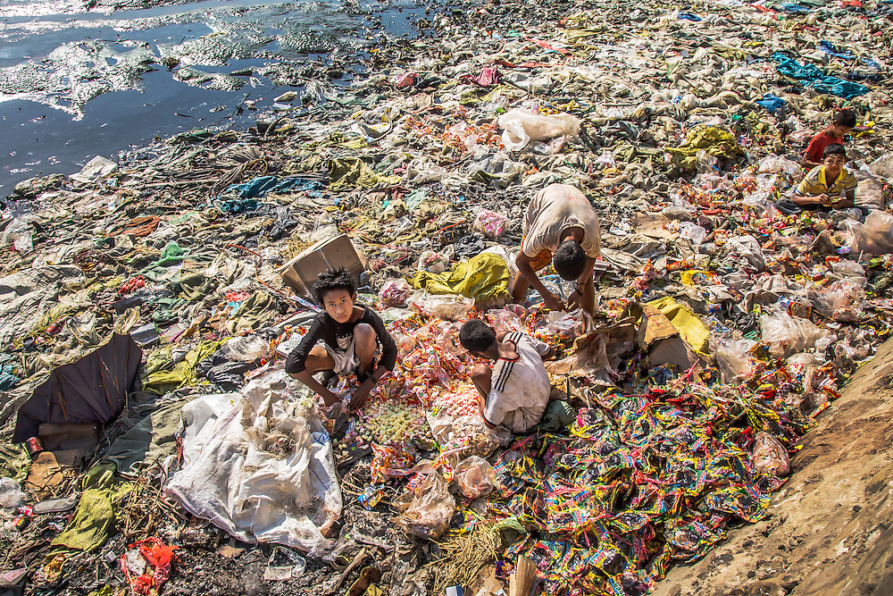Kids at the fish port in Sittwe, Rakhine State, Myanmar rummage through trash washed up on the banks of the river.