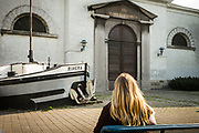 A blonde woman sitting on a bench in the harbour area, close to the Sint Salvatorchurch, Ghent, Belgium, 13.10.2015