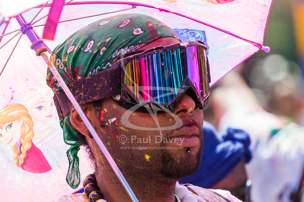 London, August 27 2017. A paint-splattered reveller with a child's umbrella on Ladbroke Grove as Family Day of the Notting Hill Carnival gets underway. The Notting Hill Carnival is Europe's biggest street party held over two days of the bank holiday weekend, attracting over a million people. © Paul Davey.