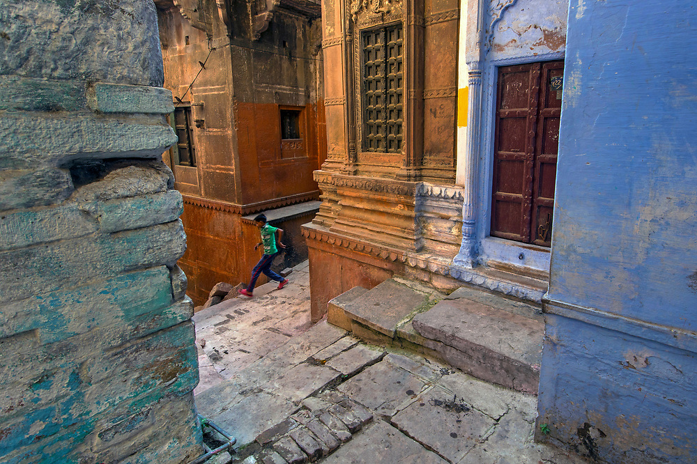 A boy retrieving the ball of a cricket game in a narrow alleyway,  old town, Varanasi