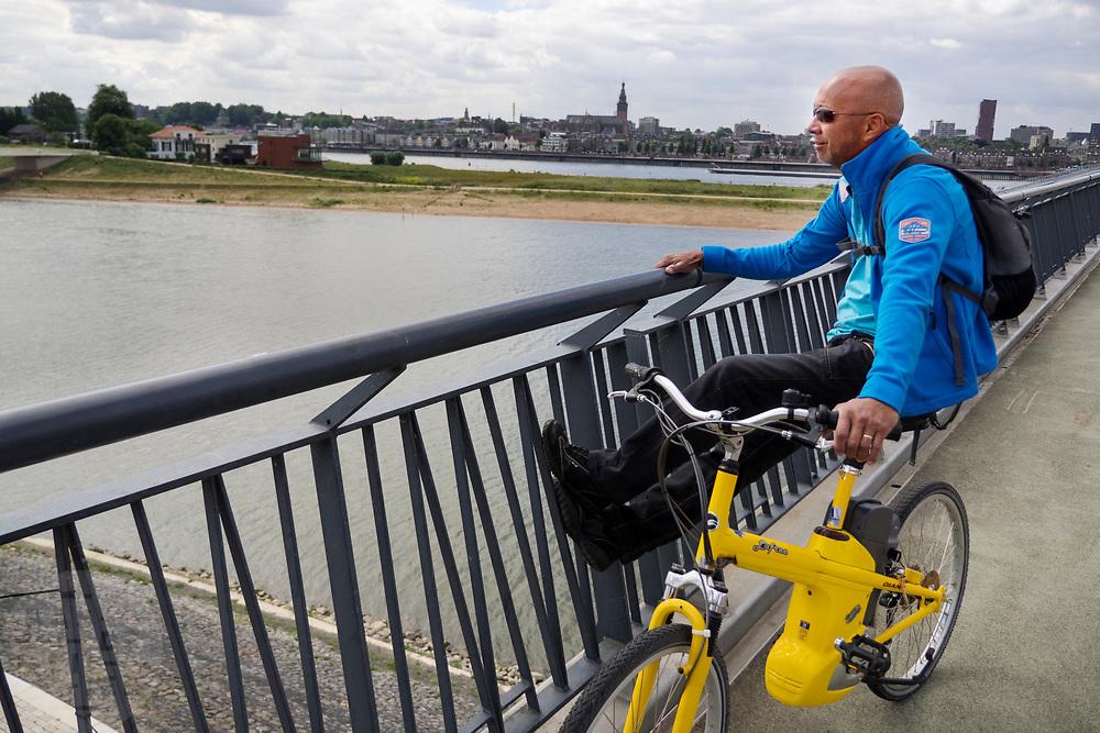 In Nijmegen kijkt een man op zijn elektrische fiets vanaf 'De Snelbinder', de fietsbrug tussen Nijmegen en Lent, over de Waal.<br /> <br /> In Nijmegen a man sits on his electric bike looking at the view of the river Waal.