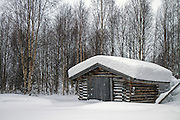 Lapland, Scandinavia, a snow covered wood shed, in a landscape of snow