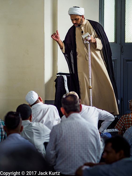 """24 NOVEMBER 2017 - YANGON, MYANMAR: An imam preaches during Friday midday prayers in Mogul Shiah Mosque in Yangon. Many Muslims in overwhelmingly Buddhist Myanmar feel their religion is threatened by a series of laws that target non-Buddhists. Under the so called """"Race and Religion Protection Laws,"""" people aren't allowed to convert from Buddhism to another religion without permission from authorities, Buddhist women aren't allowed to marry non-Buddhist men without permission from the community and polygamy is outlawed. Pope Francis is to arrive in Myanmar next week and is expected to address the persecution of the Rohingya, a Muslim ethnic minority in western Myanmar. Some Muslims and Christians are concerned that if the Pope's comments take too strong of pro-Rohingya stance, he could exacerbate religious tensions in the country.  PHOTO BY JACK KURTZ"""