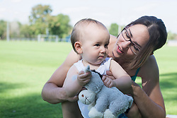 Mother with her baby boy in lawn, Munich, Bavaria, Germany