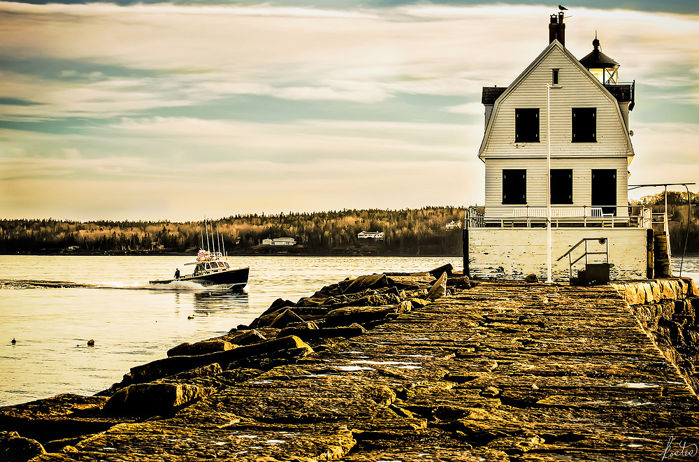 The Breakwater Light in Rockland, Maine in the late afternoon, bathed in golden light, with a Gull sitting at the very top.