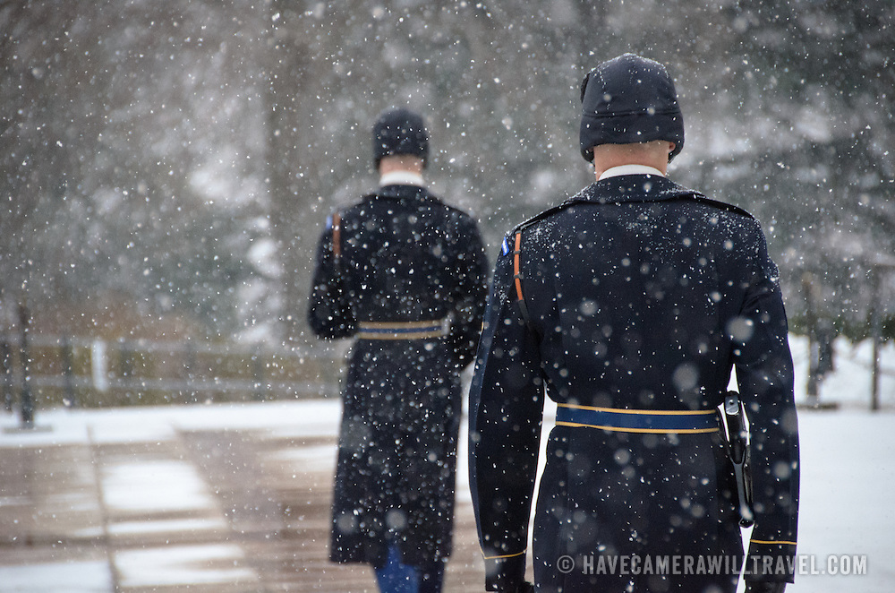 Soldiers take part in the changing of the guard ceremony at the Tomb of the Unknowns at Arlington National Cemetery in the snow. Closest to the camera is the relief commander. Behind him is the guard being relieved at the end of his shift.