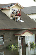 A man and a woman sit on the roof of their house in flooded New Orleans August 30, 2005. Hurricane Katrina devastated the town and surroundings and looting was reported in the area. Floodwaters engulfed much of New Orleans on Tuesday as officials feared a steep death toll and planned to evacuate thousands remaining in shelters after the historic city's defenses were breached by Hurricane Katrina. REUTERS/Rick Wilking