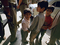 July 1997. Srinagar, Kashmir, India..Kids caught up in the conflict. Kashmiri children hold hands and stick close together as Indian troops move through the streets of the troubled region. The Indian government struggles to contain the rising insurgency amidst fears of a civil war in the region..Photo; Charlie Varley