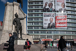 March 29, 2019 - Ankara, Turkey - On 29 March 2019, political banners depicting Turkish President Recep Tayyip Erdgoan, the Justice and Development Party's (AKP) mayoral candidate for Ankara Mehmet Özhaseki, and the Nationalist Movement Party chairman Devlet Bahçeli, hung from an office tower in the Ulus district of Ankara, Turkey, as pedestrians frequented local shops. Turkish citizens will vote in municipal elections on Sunday, 31 March 2019. (Credit Image: © Diego Cupolo/NurPhoto via ZUMA Press)