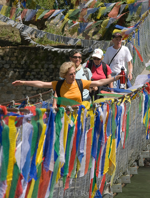 Hikers crossing a footbridge adorned with prayer flags, Punakha valley, Bhutan