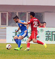 Rodrigo Paulista of Harbin Yiteng, left, challenges Wang Jiayu of Shanghai East Asia during their 28th round match of the 2014 Chinese Football Association Super League in Harbin city, northeast China's Heilongjiang province, 19 October 2014.<br /> <br /> Harbin Yiteng drew with Shanghai East Asia 1-1.