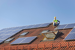 Engineer takes break from installing solar panels on house roof