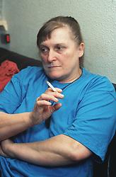 Woman sitting indoors smoking cigarette,