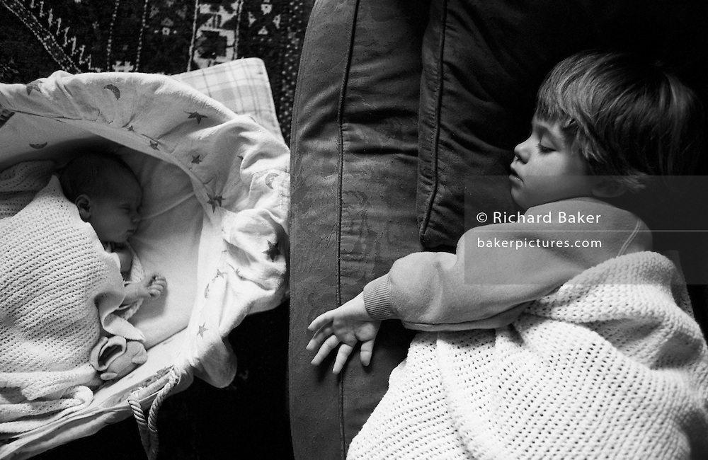 "A two and half year-old girl has a mid-afternoon sleep on the sofa of her parents' home in South London. On the floor is her young baby brother who is also enjoying some rest in his carrying basket. Both are unconscious but getting welcome shut-eye from the morning's activities. Both children face each other during deep sleep and we see the different sizes of their small hands. From a personal documentary project entitled ""Next of Kin"" about the photographer's two children's early years spent in parallel universes. Model released."