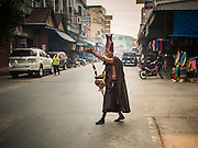 07 MARCH 2014 - MAE SOT, TAK, THAILAND:  A Burmese Buddhist hermit monk crosses a street in Mae Sot, on the Thai side of Thai-Myanmar border.    PHOTO BY JACK KURTZ