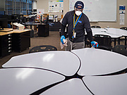 """19 MARCH 2020 - DES MOINES, IOWA:  SAM TEAH, a worker for the Des Moines Public Schools, cleans a computer arts classroom at Central Campus, a high school in the Des Moines Public Schools system. Des Moines schools are closed for at least 30 days because of the coronavirus and officials are using the time to """"deep clean"""" and sanitize each school. On Thursday morning, 19 March, Iowa reported 38 confirmed cases of the Coronavirus. Restaurants, bars, movie theaters, places that draw crowds are closed for at least 30 days. There are no """"shelter in place"""" orders in effect anywhere in Iowa but people are being encouraged to practice """"social distancing"""" and many businesses are requiring or encouraging employees to telecommute.      PHOTO BY JACK KURTZ"""