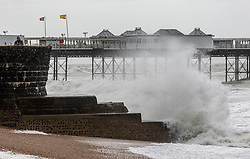 Licensed to London News Pictures. 21/05/2021. Brighton, UK. Members of the public brave the waves and high winds next to Brighton Pier on Brighton Beach as the Met Office issue weather warnings for high wind speeds and prolonged rain today. Rain and storm winds are expected today with wind speeds in excess of 55mph along the South Coast and London as the miserable May Spring weather continues. However, sun is on the way for the May Bank Holiday with temperatures expected to hit 22c by the end of the month. Photo credit: Alex Lentati/LNP
