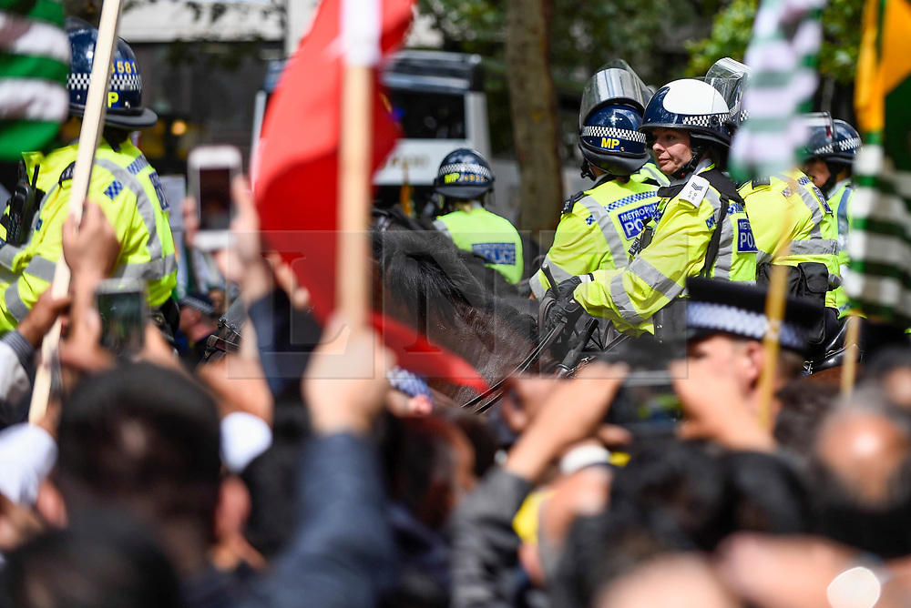 © Licensed to London News Pictures. 15/08/2019. LONDON, UK.  Mounted police stand in front of thousands of protesters, many waving Pakistani and Kashmiri flags, outside the Indian High Commission in Aldwych, on what they are calling Black Day, to stand in solidarity with the people of Kashmir.  Indian Prime Minister Narendra Modi delivered an Independence Day speech highlighting his decision to remove the special rights of Kashmir as an autonomous region.  Photo credit: Stephen Chung/LNP