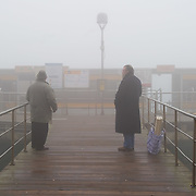 """VENICE, ITALY - JANUARY 05: Passengers wait for a """"Vaporetto"""" (Waterbus) as thick fog shrouds the city, on January 5, 2012 in Venice, Italy. Venice woke up this morning under a heavy blanket of fog adding to the atmosphere of the city."""