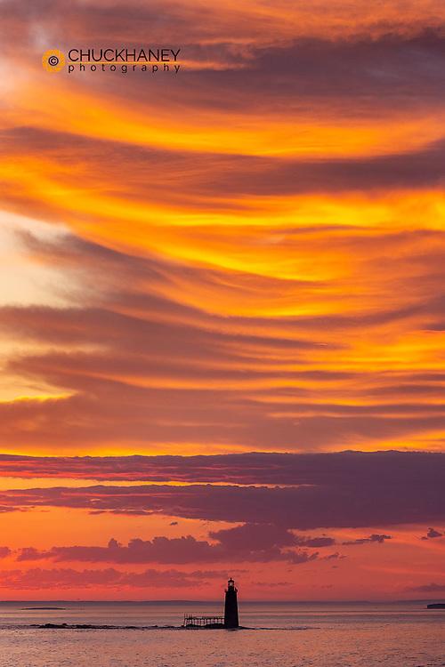 Spectacular sunrise clouds over Ram Island Ledge Lighthouse in Portland, Maine, USA