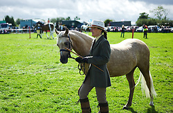 © Licensed to London News Pictures.26/08/15<br /> Egton, UK. <br /> <br /> A woman parades around the arena with her pony at the 126th Egton Show in North Yorkshire. <br /> <br /> Egton is one of the largest village shows in the country and is run by a band of voluntary helpers. <br /> <br /> This year the event featured wrought iron and farrier displays, a farmers market, plus horse, cattle, sheep, goat, ferret, fur and feather classes. There was also bee keeping, produce and handicrafts on display.<br /> <br /> Photo credit : Ian Forsyth/LNP