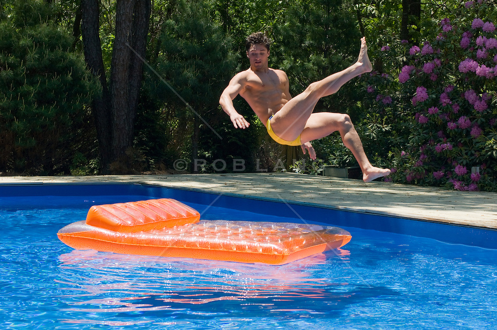 man in mid-air about to land on a float in a swimming pool