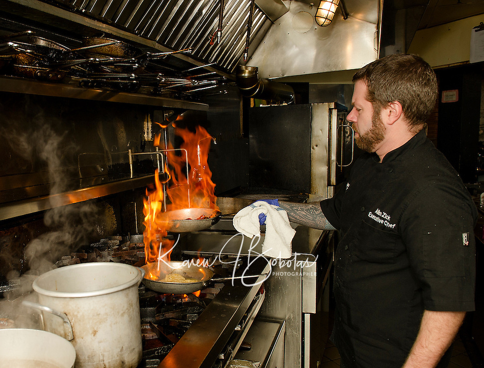Comman Man Executive Chef Allen Zick throws a flame as he prepares mussels for one of the signature dishes served at Lago's in Meredith.  (Karen Bobotas/for the Laconia Daily Sun)
