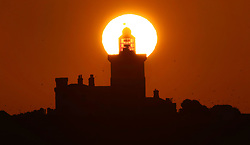 The sun rises over Coquet Island off the Northumberland Coast, as thunderstorms and potential flooding have been forecast for large parts of the UK on Tuesday, prompting weather warnings from the Met Office.