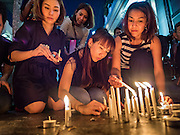 18 AUGUST 2015 - BANGKOK, THAILAND: Women light candles to honor the deceased at a makeshift memorial in front of Erawan Shrine, which was damaged by a bomb Monday night. An explosion at Erawan Shrine, a popular tourist attraction and important religious shrine in the heart of the Bangkok shopping district, killed at least 20 people and injured more than 120 others, including foreign tourists, during the Monday evening rush hour. Twelve of the dead were killed at the scene. Thai police said an Improvised Explosive Device (IED) was detonated at 18.55. Police said the bomb was made of more than six pounds of explosives stuffed in a pipe and wrapped with white cloth. Its destructive radius was estimated at 100 meters.    PHOTO BY JACK KURTZ