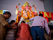 "23 SEPTEMBER 2018 - BANGKOK, THAILAND: Men move the Ganesha deity to a waiting truck at the Ganesha Festival at Wat Dan in Bangkok. The deity was put on a truck for a procession through Bangkok.  Ganesha Chaturthi also known as Vinayaka Chaturthi, is the Hindu festival celebrated on the day of the re-birth of Lord Ganesha, the son of Shiva and Parvati. The festival, also known as Ganeshotsav (""festival of Ganesha"") is observed in the Hindu calendar month of Bhaadrapada, starting on the the fourth day of the waxing moon. The festival lasts for 10 days, ending on the fourteenth day of the waxing moon. Outside India, it is celebrated widely in Nepal and by Hindus in the United States, Canada, Mauritius, Singapore, Thailand, Cambodia, and Burma.   PHOTO BY JACK KURTZ"