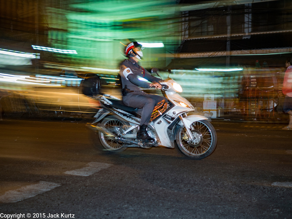 """21 DECEMBER 2015 - BANGKOK, THAILAND: A policeman on his motorbike on the street in front of Pak Khlong Talat, also called the Flower Market. The market has been a Bangkok landmark for more than 50 years and is the largest wholesale flower market in Bangkok. A recent renovation resulted in many stalls being closed to make room for chain restaurants to attract tourists. Now Bangkok city officials are threatening to evict sidewalk vendors who line the outside of the market. Evicting the sidewalk vendors is a part of a citywide effort to """"clean up"""" Bangkok.       PHOTO BY JACK KURTZ"""