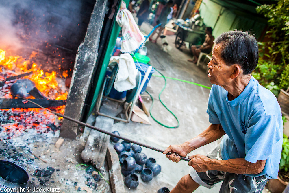 """03 DECEMBER 2012 - BANGKOK, THAILAND:  A bowl maker fires monks' bowls, called """"bat"""" (pronounced with a long """"a"""" as in baat) on Soi Baan Bat in Bangkok. The bowls are made from eight separate pieces of metal said to represent the Buddha's Eightfold Path. The Monk's Bowl Village on Soi Ban Baat in Bangkok is the only surviving one of what were originally three artisan's communities established by Thai King Rama I for the purpose of handcrafting """"baat"""" the ceremonial bowls used by monks as they collect their morning alms. Most monks now use cheaper factory made bowls and the old tradition is dying out. Only six or seven families on Soi Ban Baat still make the bowls by hand. Most of the bowls are now sold to tourists who find their way to hidden alleys in old Bangkok. The small family workshops are only a part of the """"Monk's Bowl Village."""" It is also a thriving residential community of narrow alleyways and sidewalks.  PHOTO BY JACK KURTZ"""