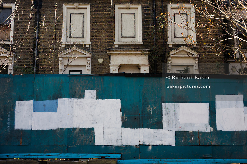 A derelict Victorian house boarded-up with similar patterns to that of blanked off windows and door pediment.