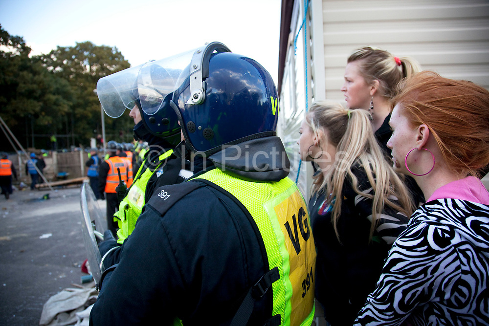 Traveller girls look on next to riot police. Protesters who barricaded themselves above the entrance to the Dale Farm travellers' site have been removed by police as bailiffs prepare to move in. Essex Police cleared the scaffolding structure so it could be dismantled and machinery driven in by bailiffs to evict the travellers. On Wednesday night Essex Police said that over the course of the day 23 people had been arrested. Clearance of Dale Farm prior to eviction. Riot police and bailiffs were present on 19th October 2011, as a scaffolding gantry was cleared of protesters so the site could be cleared. Dale Farm is part of a Romany Gypsy and Irish Traveller site on Oak Lane in Crays Hill, Essex, United Kingdom. Dale Farm housed over 1,000 people, the largest Traveller concentration in the UK. The whole of the site is owned by residents and is located within the Green Belt. It is in two parts: in one, residents constructed buildings with planning permission to do so; in the other, residents were refused planning permission due to the green belt policy, and built on the site anyway.