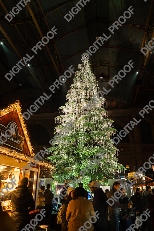Zurich, Switzerland - December 22, 2018 Natural christmas tree and vendor stands with visitors at Christmas market held at the train central station in Zurich