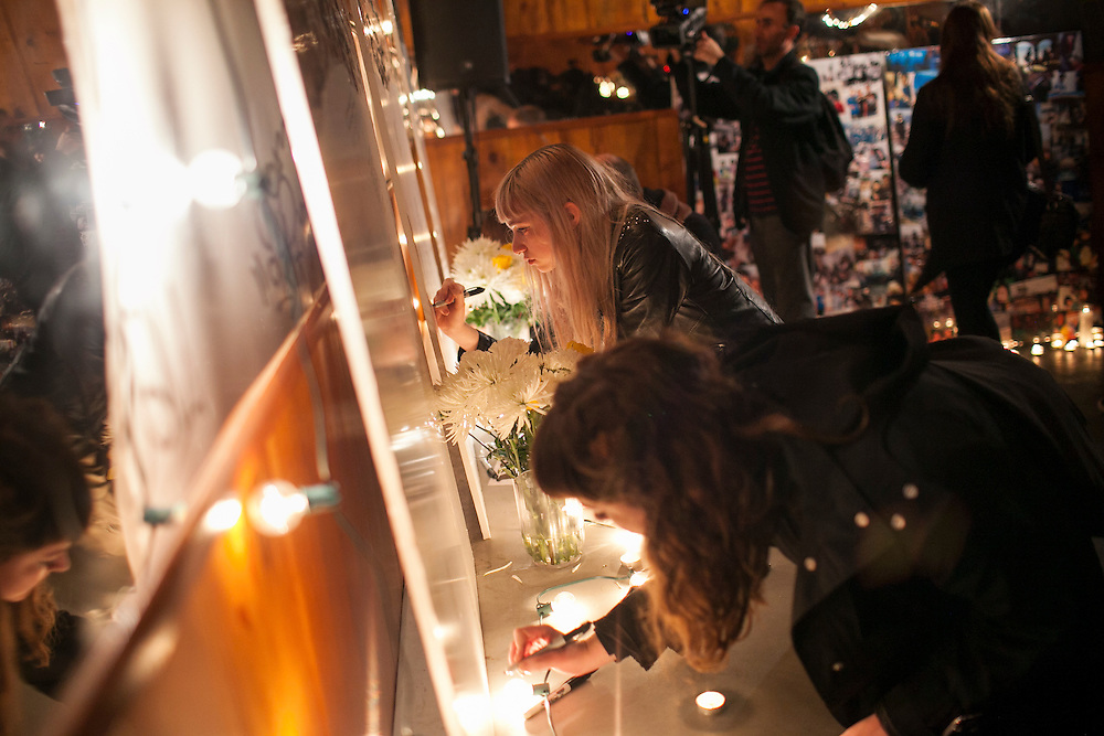 People write messages on a memorial at a candlelight vigil for the Yellow Dogs, the band whose members were killed last week, at Cameo Gallery, 93 North 6th Street in the Williamsburg neighborhood of Brooklyn, NY on Monday, Nov. 18, 2013.<br /> <br /> Photograph by Andrew Hinderaker