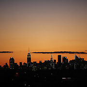 The Manhattan skyline at sunset showing the Empire State Building, (highest point, left) and the Chrysler building shot from the Arthur Ashe Tennis Stadium, Queens New York, USA. 4th September 2013. Photo Tim Clayton