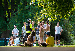 © Licensed to London News Pictures; 02/06/2020; Bristol, UK. A police officer speaks to groups of more than six young people in St Andrews Park in the evening, after some lockdown restrictions due to the coronavirus covid-19 pandemic have been lifted by the UK Government earlier this week. Under the new rules people can spend as long outdoors as they want and can meet in groups of up to six people from different households as long as they maintain social distancing of 2m or more between members of different households. Photo credit: Simon Chapman/LNP.