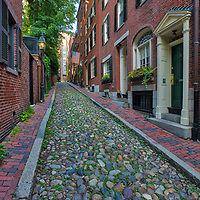 Historic Boston photography image of old colonial brick row houses along romantic Acorn Street on a beautiful late afternoon. Acorn Street is located near Louisburg Square, the most prestigious address in Beacon Hill. Street lanterns provide a warm light in Beacon Hill. Acorn Street is often noted as the most frequently photographed street in the USA. It is a narrow lane paved with cobblestones that was home to coachmen employed by families in Mt. Vernon and Chestnut Street mansions.<br />