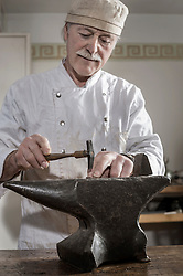 Senior craftsman shaping of copper ring at workshop, Bavaria, Germany