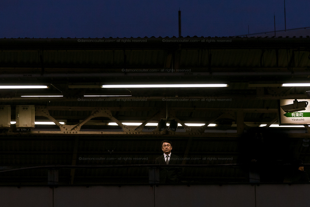 A salaryman or Japanese male office worker waiting at Shimbashi station , Tokyo Japan, Wednesday, December 10th 2008