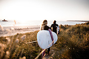 Couple holding surfboards, walking through the sand dunes in golden sunlight at Le Braye, St Ouen's Bay, Jersey, CI