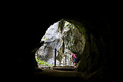 Seen through one of the tunnels, a visitor peers down into Tolmin Gorge Tolminska Korita, on 20th June 2018, in Tolmin Gorge , Slovenia.