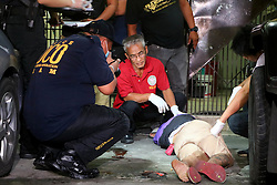 """September 30, 2016 - Philippines - (EDITORS NOTE: Image depicts death.) Members of S.O.C.O. (Scene of the Crime Operatives) process the crime scene and the remain of unidentified suspect after was pin down by the members of Philippine National Police (PNP) after the gun battle in Sta. Cruz Manila City. S.O.C.O. team members found a small sachet of methamphetamine """"shabu"""" on the pocket of suspect. (Credit Image: © Gregorio B. Dantes Jr/Pacific Press via ZUMA Wire)"""