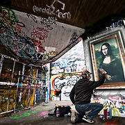 A graffiti artist at work creating a version of the Mona Lisa masterpiece against a busy urban background.