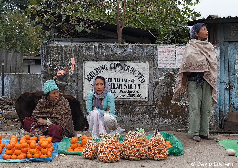 Women selling oranges in small bamboo baskets along a street in Pasighat. Oranges from Arunachal Pradesh are famous for their delicious taste.